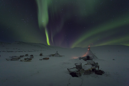 Winter night landscape with sledges, tent and polar lights in the sky. The Yamal Peninsula. Russia Stock Photo