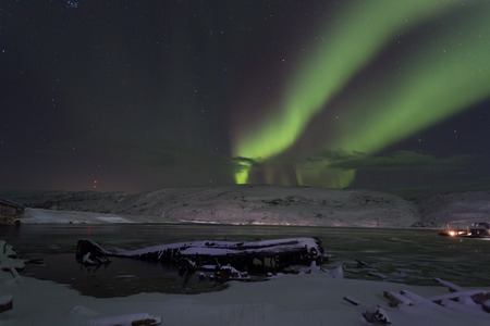 Old  boat on a background of aurora in winter Stock Photo