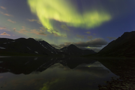 Aurora in the night sky cut the mountains, reflected in the water. Yamal. Russia
