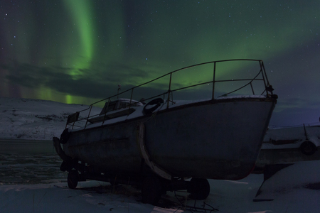 Old fishing ship on a background of aurora in winter