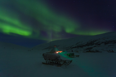 Winter night landscape with sledges, tent and aurora in the sky.  Yamal. Russia