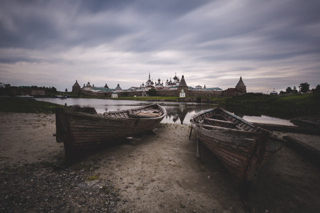 Two old wooden boats on the background of the Solovetsky Monastery, Russia