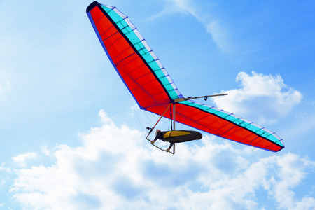 The hang glider on a red hang-glider is flying in a blue sky