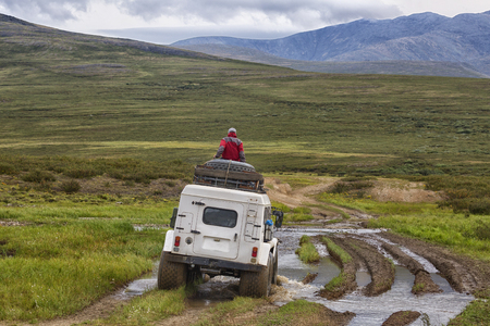 A man sits on the roof of a white all-terrain vehicle riding along the tundra