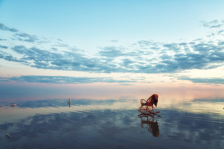 chair stands in the water of the lake, the salt lake of Elton at sunset