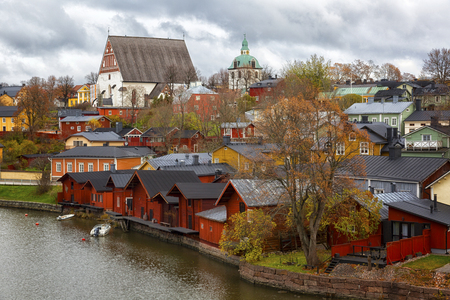 Red shore houses on the riverbank of Porvoo river. Old town of Porvoo in Finland in autumn. Фото со стока