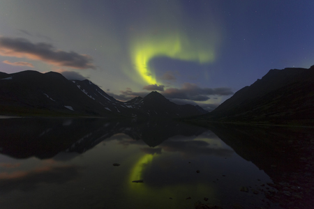 Aurora in the night sky cut the mountains, reflected in the river Hadata. Yamal. Russia