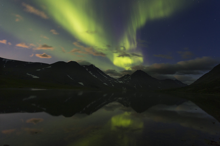 Aurora in the night sky cut the mountains, reflected in the lace. Yamal. Russia