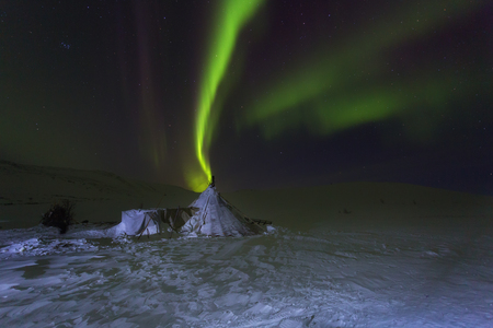 Winter night landscape with sledges, tent and aurora borealis in the sky. The Yamal Peninsula. Russia