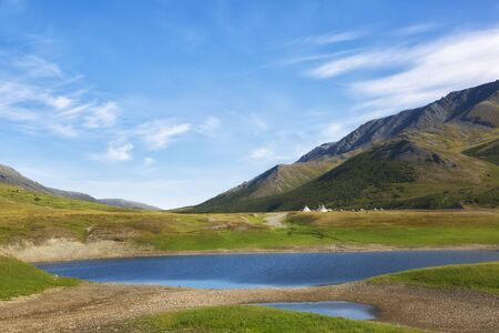 Landscape with a lake in the foreground, chums and mountains on a summer day Stock Photo
