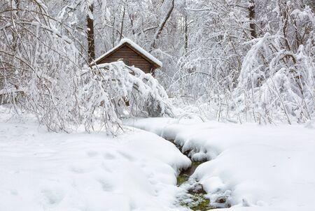 Paisaje invernal con una casa y un río.
