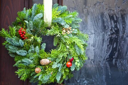Christmas wreath of fir branches and bright toys on the door