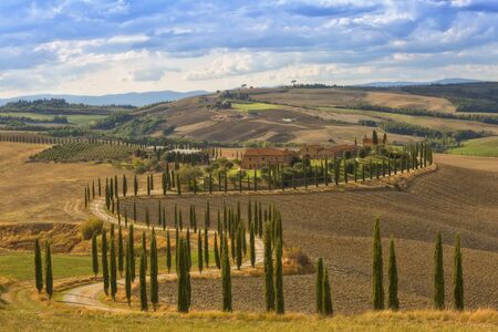 Landscape of hills, country road, cypresses trees and rural houses,Tuscany