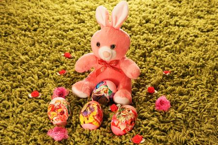 pasto sintetico: Huevos de Pascua con el conejo de juguete de color rosa colocados en c�sped sint�tico verde con flores