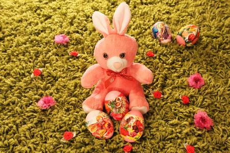 prato sintetico: Uova di Pasqua con rosa coniglio giocattolo immessi in erba sintetica verde con fiori