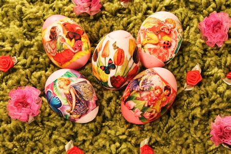 pasto sintetico: Huevos de Pascua con im�genes de flores y mariposas colocadas en una hierba verde sint�tico Foto de archivo