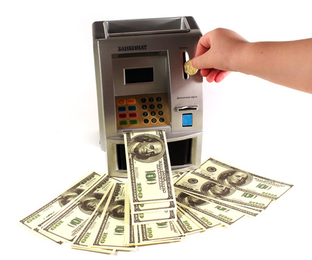 Child hand throwing 20 cents in the treasury in the form of an ATM and get 100 dollar notes
