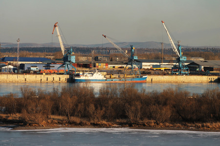 tonnage: Cranes, containers, barges in a cargo port on the river Stock Photo