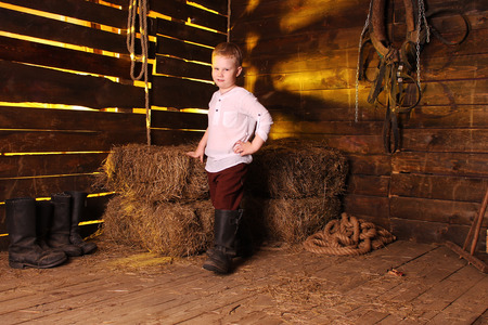 barn boots: Child in a white shirt, trousers and boots at the background of haystacks