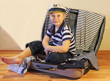 funny boy: Boy in a sailor dress sitting in a suitcase with clothes in a marine style