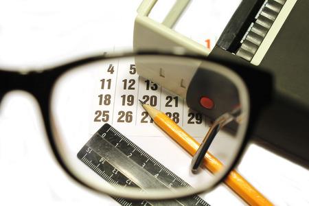 an eyepiece: Still life of calendar sheet, stamp, pencil and ruler viewed through the glasses eyepiece