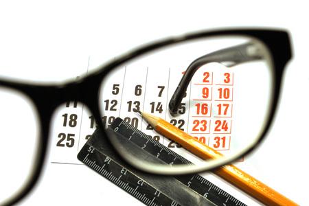 an eyepiece: Still life of calendar sheet, pencil and ruler viewed through the glasses eyepiece