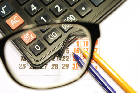 an eyepiece: Still life of calendar sheet, calculator, pencil and ruler viewed through the glasses eyepiece glasses Stock Photo
