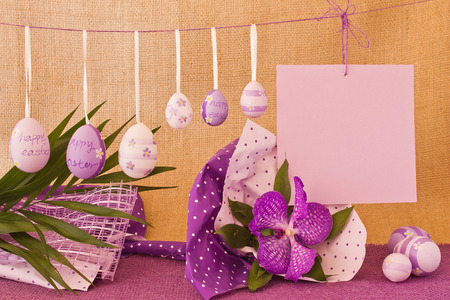 congratulatory: Eggs and congratulatory sheet hanging on a rope on the background of a sacking and violet orchid