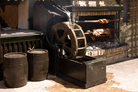 pollo rostizado: Rotisserie with pig and chicken over the coals, spinning by water wheel