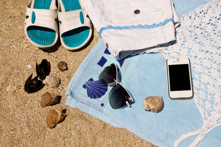 towel beach: Frame made of seashells, beach towel, beach slippers, sunglasses, T-shirts, shorts and phone on the sand