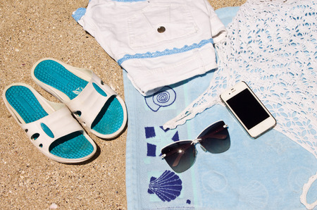 towel beach: Background of beach towel, beach slippers, sunglasses, T-shirts, shorts and phone on the sand Stock Photo