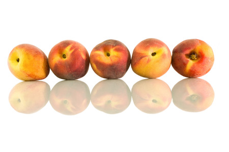 velvety: Peaches arranged in a row and its reflection on a white isolated background