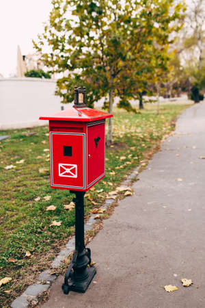 Red metal mailbox on the street. Blurred background