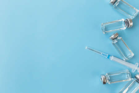 Medicine treatment, vaccination concept. Bottles with vaccine, antibiotic, injection, syringe on blue background. High quality photo