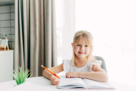 A little smiling girl sits at the table and writes in a white notebook. Education concept. Home schooling. Homework. Smiling face. High quality photo