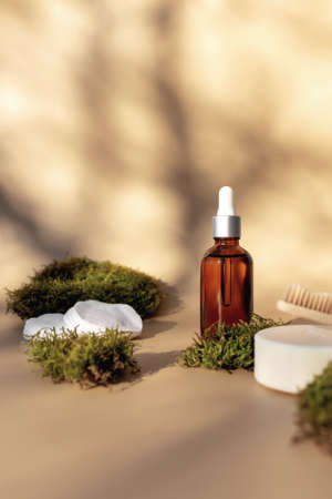 Healthcare concept of bath accessories with bottle of essential oil, wooden tooth brush, soap and cotton pads on beige background and green moss as eco zero waste, plastic free environment concept