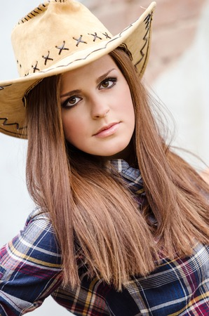 Cowgirl with  hat in the western town photo