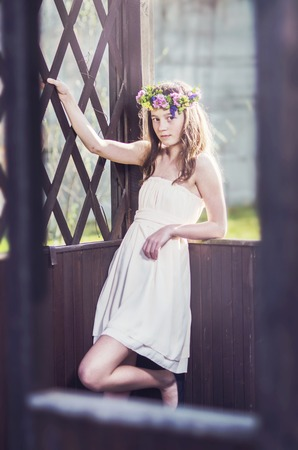 Romantic beautiful girl with flower wreath in the garden