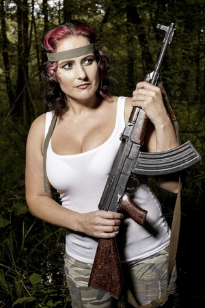 sexy army: The young army woman with gun in the forest - mission Stock Photo