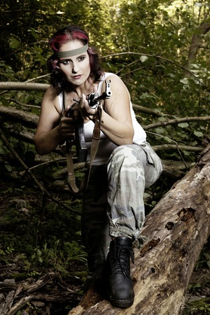 The young army woman with gun in the forest - mission photo