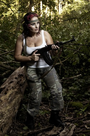 army girl: The young army woman with gun in the forest - mission Stock Photo