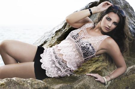 Das schöne Mädchen auf den Felsen am Meer liegen