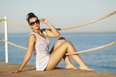 The beautiful girl with sunglasses sitting on the pier Standard-Bild