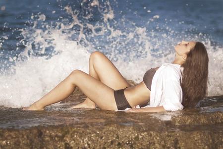 Die schönen Mädchen am Ufer des Meeres in Wellen liegen