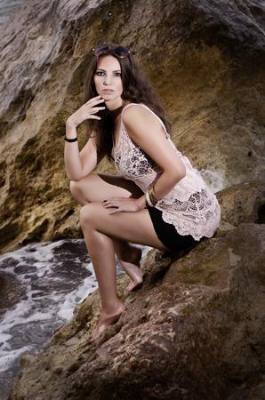 Das schöne Mädchen sitzt auf dem Felsen am Meer