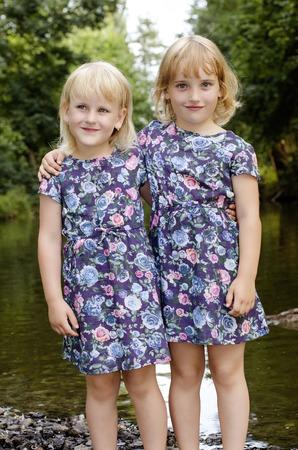 zwei Schwestern in geblümten Kleid durch den Fluss gekleidet Lizenzfreie Bilder