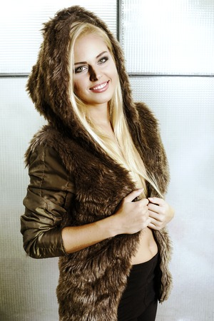 Attractive blonde girl with long hair dressed in a fur coat with  with hood Standard-Bild