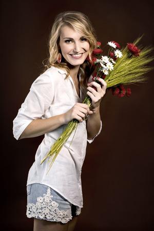 Glückliches schönes Mädchen mit der Kunststoff rote Mohnblumen und Maiskolben Lizenzfreie Bilder