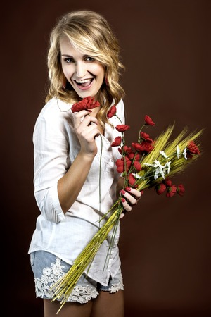 Happy and funny beautiful girl holding the  plastic red poppies and corn cobs