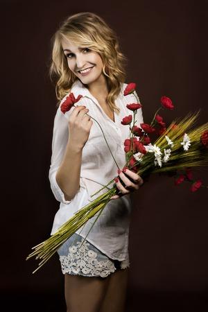Glücklich und lustig schönen Mädchen, die die Kunststoff roten Mohnblumen und Maiskolben